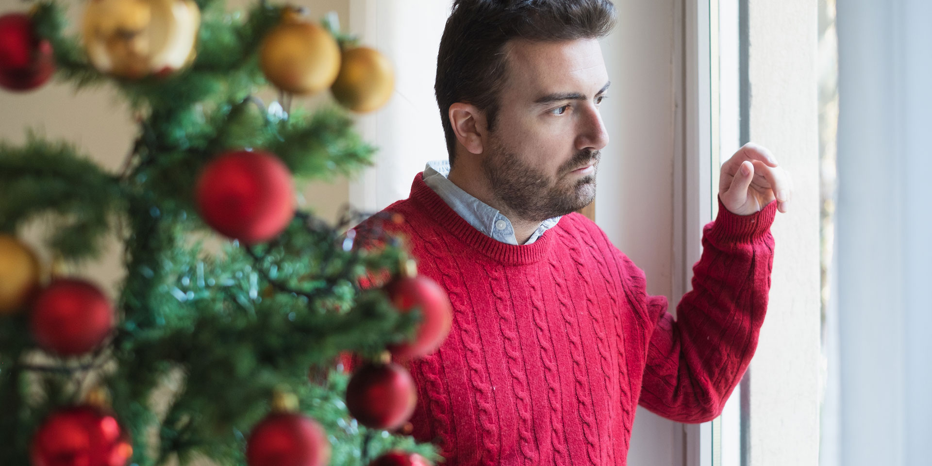 man looking on the window at christmas time